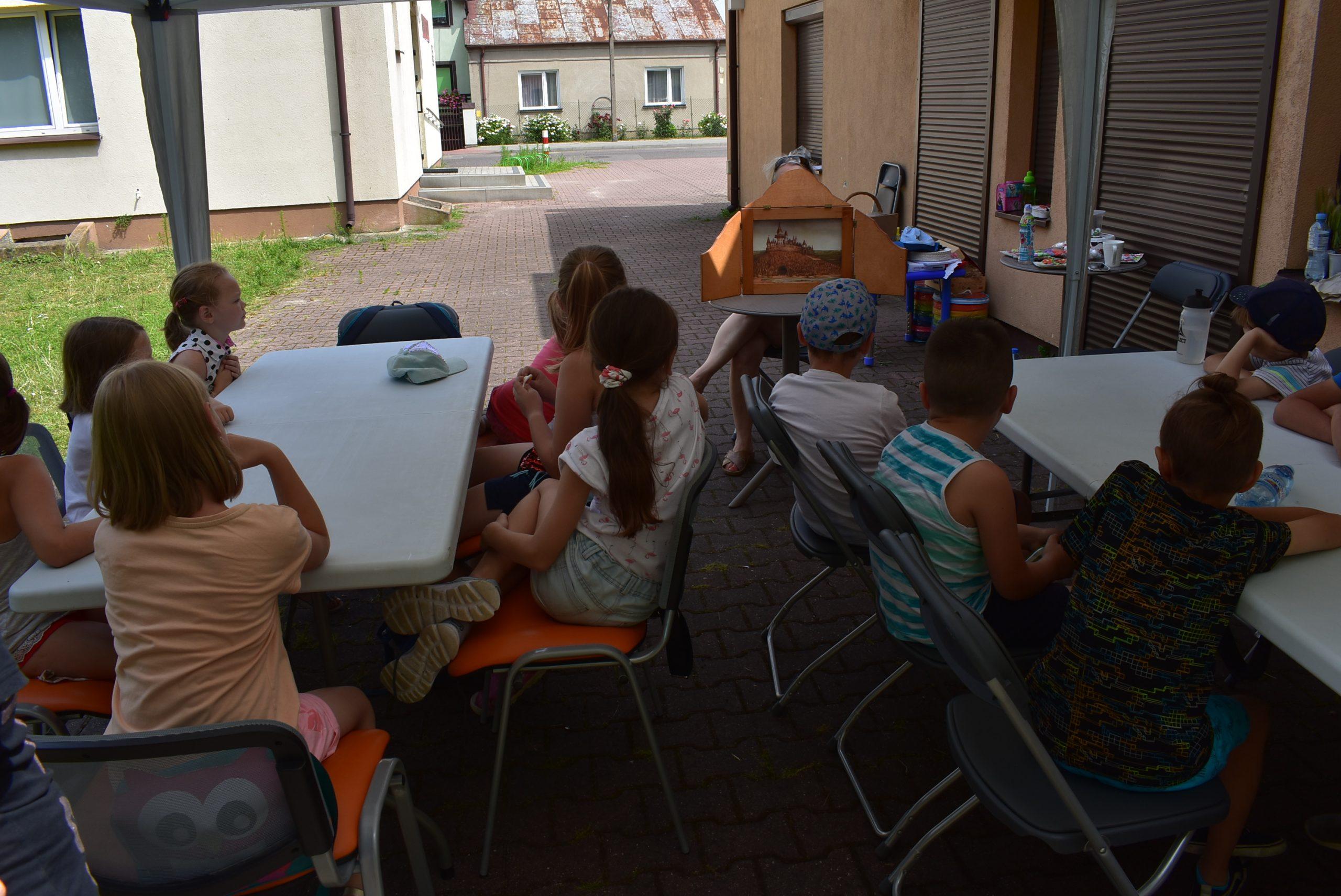 Dzieci słuchają teatrzyku Kamishibai.