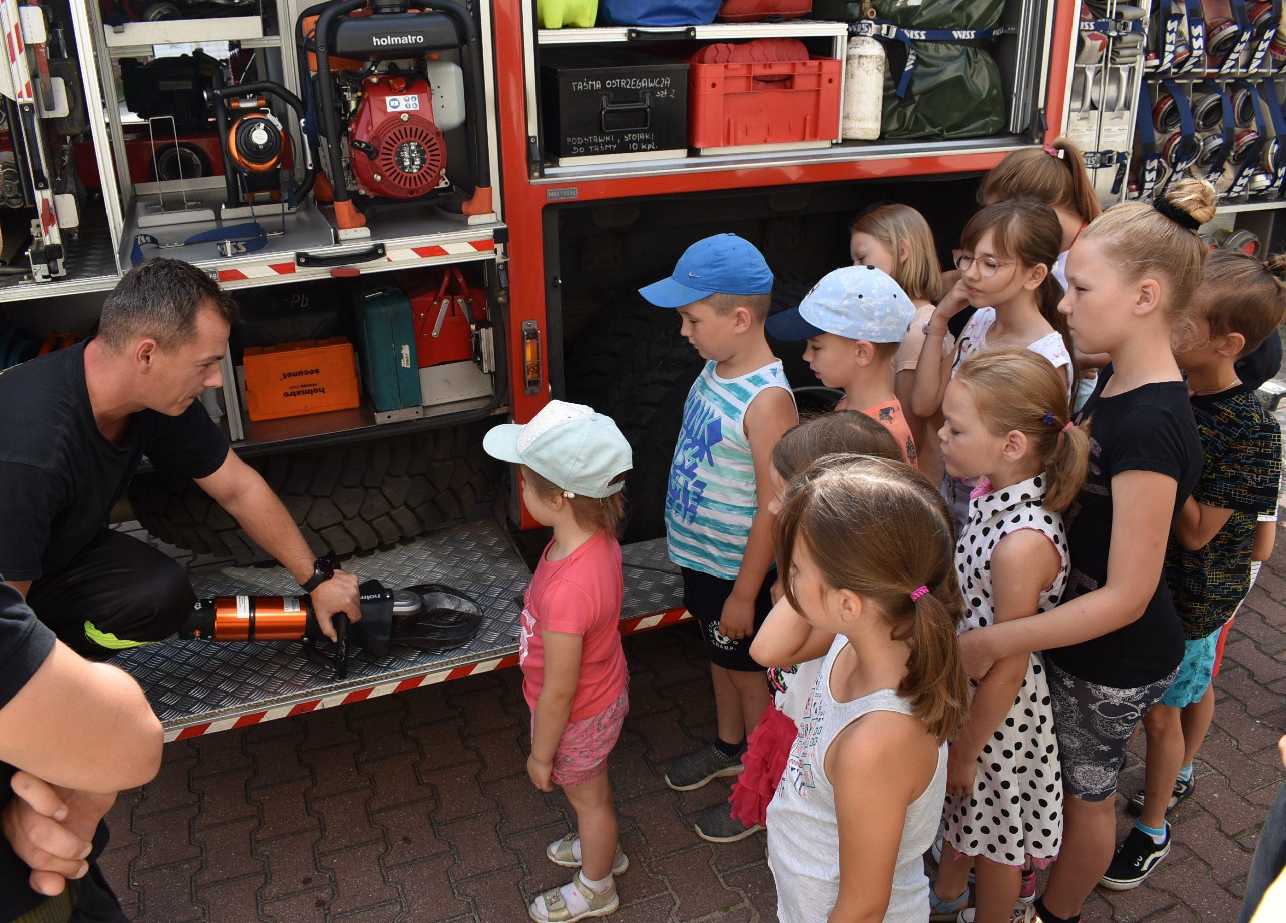 Strażak pokazuje dzieciom nożyce docięcia metalu.