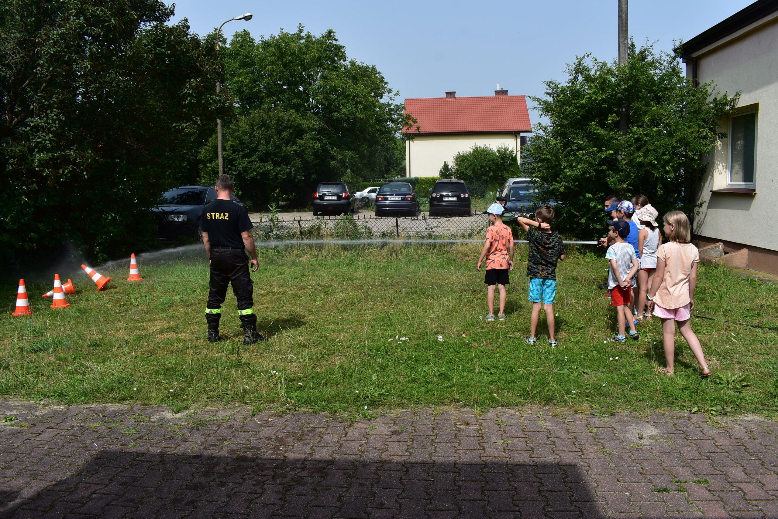 Dzieci próbują trafić wpachołki zapomocą wody zestrażackiej sikawki.