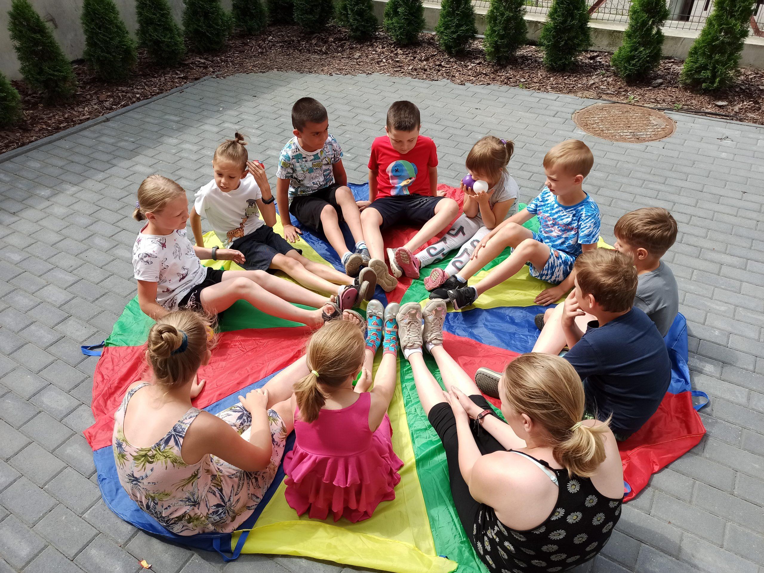 Dzieci siedzą napodwórku obok Oddziału dla dzieci imłodzieży.