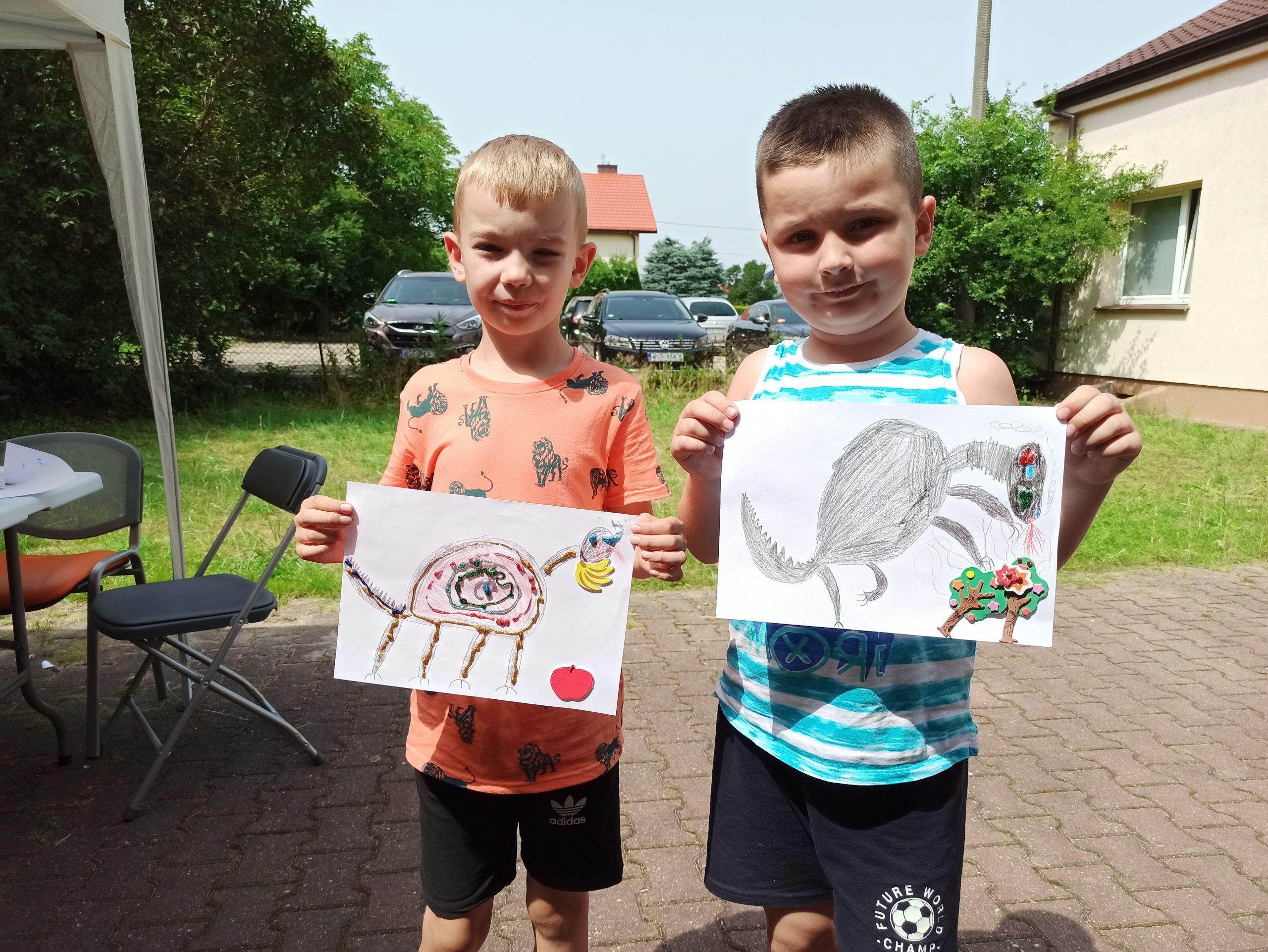 Chłopcy pokazują wykonane przezsiebie prace plastyczne.